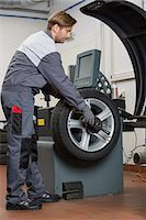 Side view of male mechanic repairing car's wheel in workshop Stock Photo - Premium Royalty-Freenull, Code: 693-07672924
