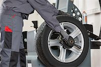 Midsection of male mechanic repairing car's wheel in repair shop Stock Photo - Premium Royalty-Freenull, Code: 693-07672925