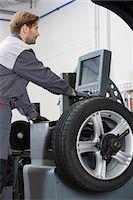 Side view of mid adult male mechanic repairing car's wheel in workshop Stock Photo - Premium Royalty-Freenull, Code: 693-07672926