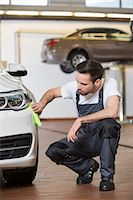 Full length of automobile mechanic cleaning car in workshop Stock Photo - Premium Royalty-Freenull, Code: 693-07672929