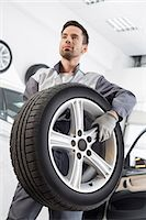 Young maintenance engineer carrying tire in automobile store Stock Photo - Premium Royalty-Freenull, Code: 693-07672960