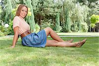 Full length of smiling young woman relaxing on grass in park Stock Photo - Premium Royalty-Freenull, Code: 693-07673031