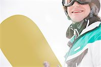 sports and snowboarding - Smiling young man holding snowboard Stock Photo - Premium Royalty-Freenull, Code: 693-07673097