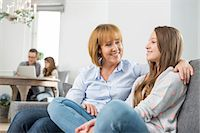 affectionate mother and daughter sitting on sofa with family in background Stock Photo - Premium Royalty-Freenull, Code: 693-07673194