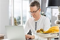 Mature man using laptop at table in house Stock Photo - Premium Royalty-Freenull, Code: 693-07673207