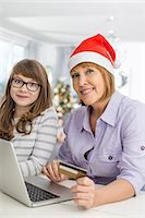 Portrait of mother and daughter shopping online during Christmas Stock Photo - Premium Royalty-Freenull, Code: 693-07673223