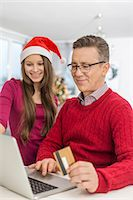 ebusiness - Smiling father and daughter shopping online at home during Christmas Stock Photo - Premium Royalty-Freenull, Code: 693-07673227