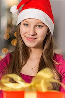 preteen  smile  one  alone - Close-up portrait of smiling girl wearing Santa hat Stock Photo - Premium Royalty-Freenull, Code: 693-07673235