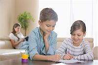 Siblings drawing together at table with mother in background Stock Photo - Premium Royalty-Freenull, Code: 693-07673281