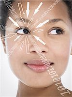 Close-up of smiling businesswoman with binary digits and arrow signs moving towards her eye against white background Stock Photo - Premium Royalty-Freenull, Code: 693-07673290