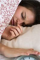 Woman lying in bed, silencing alarm clock Stock Photo - Premium Royalty-Free, Artist: Laurie Rubin, Code: 632-07674723