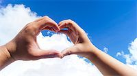 A couple made a heart shape from each other hand in the sky Stock Photo - Royalty-Freenull, Code: 400-07679181