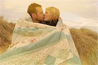 Couple kissing under blanket on beach Stock Photo - Premium Royalty-Freenull, Code: 6122-07692369