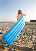 Boy inflating lilo on beach Stock Photo - Premium Royalty-Freenull, Code: 6122-07692677