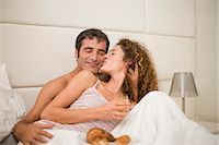 Smiling couple having breakfast in bed Stock Photo - Premium Royalty-Freenull, Code: 6122-07694003
