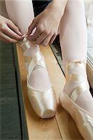 Girl tying ballet shoes Stock Photo - Premium Royalty-Freenull, Code: 6122-07695437