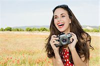 Young woman with camera in poppy field Stock Photo - Premium Royalty-Freenull, Code: 6122-07695477