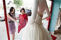 Mother and daughter looking at wedding dress in shop window Stock Photo - Premium Royalty-Freenull, Code: 6122-07695838