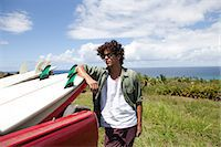 Young man leaning against surfboard in car, portrait Stock Photo - Premium Royalty-Freenull, Code: 6122-07696953
