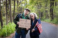 savings - Senior couple holding sign in forest, portrait Stock Photo - Premium Royalty-Freenull, Code: 6122-07698446