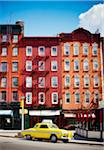 Traditional red brick buildings and old car in the trendy Chelsea district, Manhattan, New York City, NY, USA