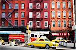 Traditional red brick buildings with old car and firetruck on street in the trendy Chelsea district, Manhattan, New York City, NY, USA