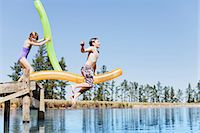 Children jumping into lake from jetty Stock Photo - Premium Royalty-Freenull, Code: 6122-07699457