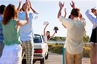 Bride waving to wedding party from car Stock Photo - Premium Royalty-Freenull, Code: 6122-07700573