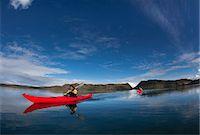 Man rowing canoe in still lake Stock Photo - Premium Royalty-Freenull, Code: 6122-07703238