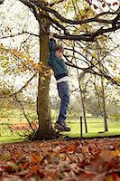Boy playing on tree outdoors Stock Photo - Premium Royalty-Freenull, Code: 6122-07703248