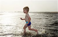 Boy playing in water at beach Stock Photo - Premium Royalty-Freenull, Code: 6122-07703288