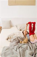 Girl getting dressed on bed Stock Photo - Premium Royalty-Freenull, Code: 6122-07703518