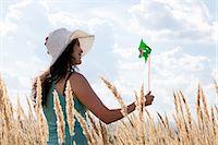 Woman holding pinwheel in wheatfield Stock Photo - Premium Royalty-Freenull, Code: 6122-07703527