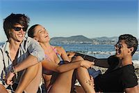 Friends laughing on rocky beach Stock Photo - Premium Royalty-Freenull, Code: 6122-07703715
