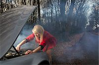 Woman looking under hood of car Stock Photo - Premium Royalty-Freenull, Code: 6122-07704306