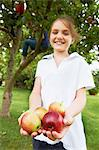 Smiling girl holding fruit outdoors