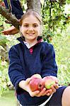Smiling girl offering fruit in tree