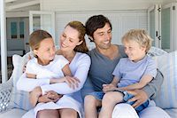 Family relaxing on sofa together Stock Photo - Premium Royalty-Freenull, Code: 6122-07705575