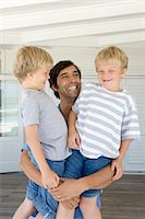 Smiling father holding sons Stock Photo - Premium Royalty-Freenull, Code: 6122-07705578