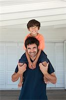 Father carrying son on shoulders Stock Photo - Premium Royalty-Freenull, Code: 6122-07705582