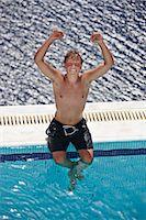 shirtless teen boy - Man cheering on edge of swimming pool Stock Photo - Premium Royalty-Freenull, Code: 6122-07705966