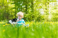 Boy with dog in field of tall grass Stock Photo - Premium Royalty-Freenull, Code: 6122-07706771
