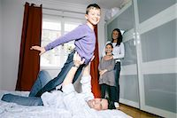 Father and son playing on bed Stock Photo - Premium Royalty-Freenull, Code: 6122-07707202