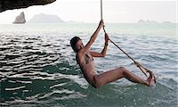 Girl playing on rope over water Stock Photo - Premium Royalty-Freenull, Code: 6122-07707454