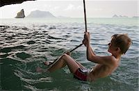Boy playing on rope over water Stock Photo - Premium Royalty-Freenull, Code: 6122-07707455