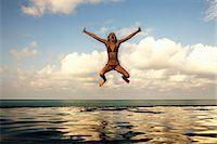 Girl jumping into infinity pool Stock Photo - Premium Royalty-Freenull, Code: 6122-07707460