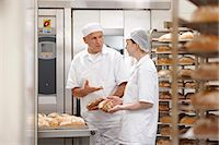 Chefs talking at oven in kitchen Stock Photo - Premium Royalty-Freenull, Code: 6122-07707499