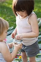 Girl and toddler sister holding jar with green anole lizard in garden Stock Photo - Premium Royalty-Freenull, Code: 614-07708250