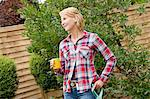 Mature woman having coffee break in garden