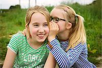 preteen girl pigtails - Nine year old girl whispering to sister in field Stock Photo - Premium Royalty-Freenull, Code: 649-07710660